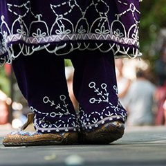 Close-up colour photograph of a woman's feet wearing a purple traditional dress, decorated with white beads.