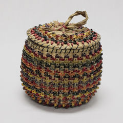 Colour photograph of an ash basket decorated with several colors. The handle of the lid is made of sweetgrass.