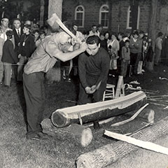 Black and white photograph of two men beating a tree trunk with the back of their axes. A crowd watches them.