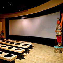 Colour photograph of a screening room: a giant screen, some benches and two sculptures representing two Abenakis.