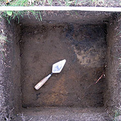 Colour photograph of an archeological test pit (squared-shape hole) where a blackened area and a trowel are shown.