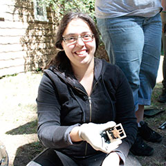Colour photograph of a young trainee archaeologist holding a shoe buckle in her hand.