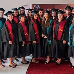Colour photograph of twenty students during their graduation ceremony. They are all wearing a gown with a red or green scarf and a mortarboard.
