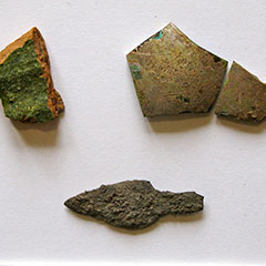 Colour photograph of a shard of glass, a piece of terracotta and an iron arrowhead.