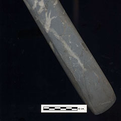 Color photograph of an elongated stone with a concave end.