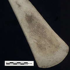 Colour photograph of an elongated polished stone. Its top is narrower than its low end.