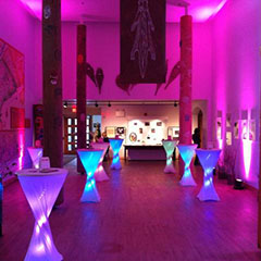 Colour photograph of the hall at the Musée des Abénakis with a pinkish light atmosphere.