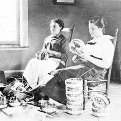 Black and white photograph of three Abenaki, sitting near a window, making baskets.